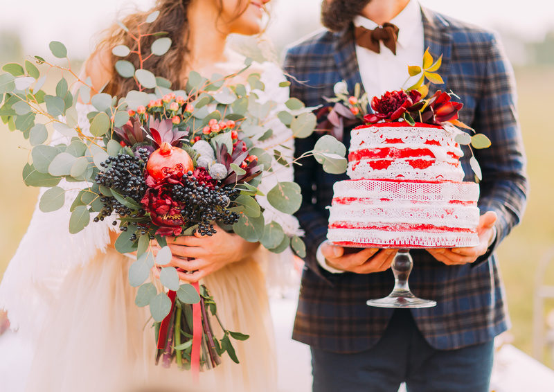 Wedding couple holds beautiful cake and bouquet close up.