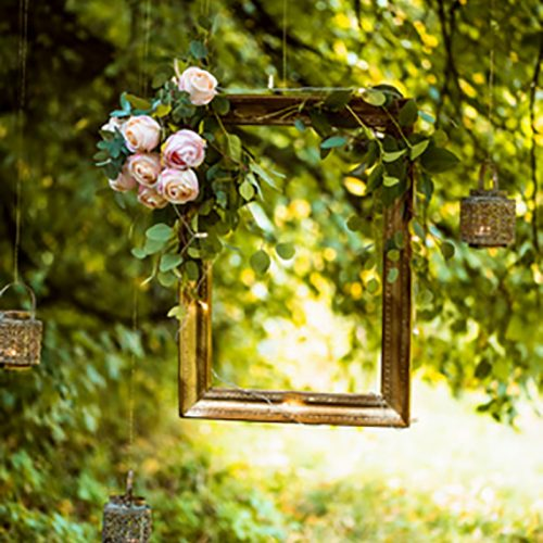Old Golden frame, decorated with flowers, hanging on a branch on green background. Floral decor for wedding photo shoot