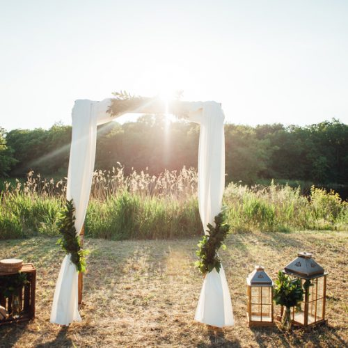 Wedding ceremony decoration in sunset. with wooden chairs